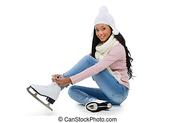 Smiling afro-American woman wearing skates while sitting on...