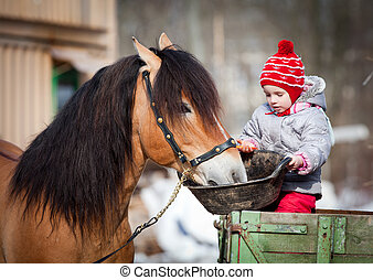 Child feeding a horse in winter - Child feeding a horse,...