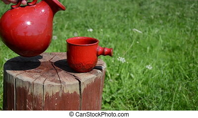 jug and cup - old clay jug with small red cup stands on a...