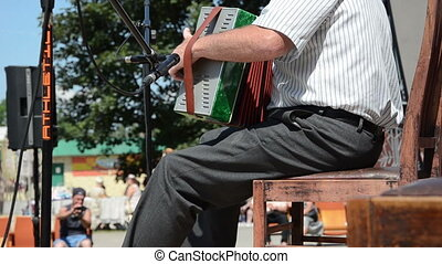 senior man accordion - senior man sitting on chair and plays...