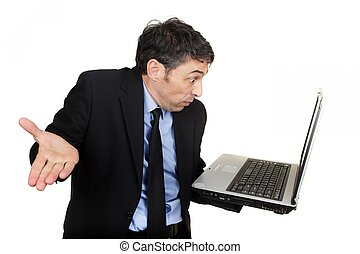 Businessman shrugging as he reads his laptop - Businessman...