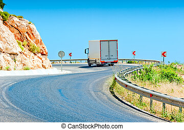 truck driving on a mountain road on a sunny day
