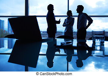 Business conversation - Three office workers interacting by...