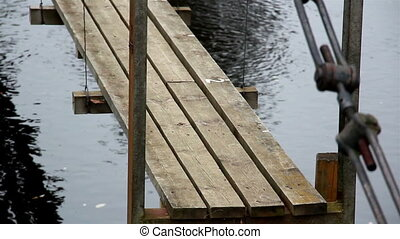 Closer image of the wooden hanging bridge The pathway in the...