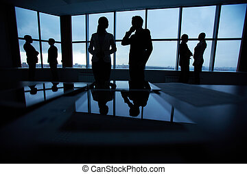Communicating in office - Silhouettes of several colleagues...