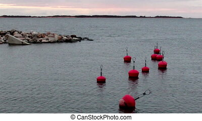 Buoy floating near the shore. There are nine buoys that are...