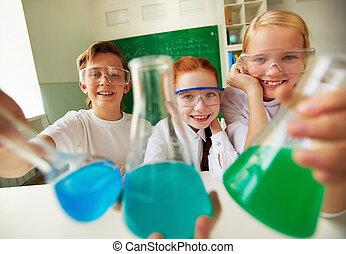 Happy pupils - Three happy schoolchildren holding tubes with...