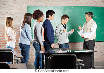 Professor Gesturing Thumbs up To Student In Classroom -...