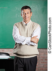 Professor Standing Arms Crossed In Classroom - Portrait of...