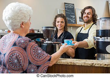 Waitress With Colleague Serving Coffee To Woman At Counter -...