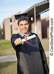 Man In Graduation Gown Showing Diploma On University Campus
