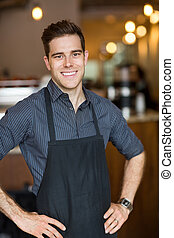 Happy Male Owner Standing In Cafe - Portrait of happy male...