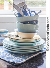 Crockery - A pile of crockery on the kitchen worktop, with...