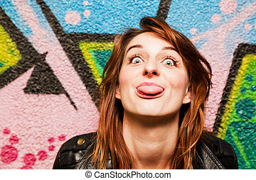 Stylish girl poking out her tongue against graffiti wall -...