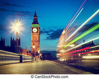 London, the UK. Red bus in motion and Big Ben at night -...