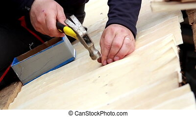 Person nailing a cedar wooden shingle shake wood plank -...