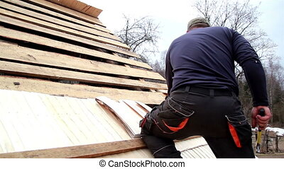 Roofer nailing the wooden roof tiles on the cedar wooden...