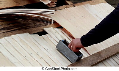 Cedar wooden shingle shake roofer getting nails from the box...