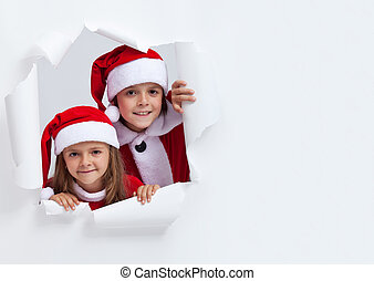 Happy kids in santa outfits looking through hole in paper -...