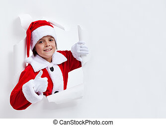 Happy santa costume boy leaning through paper hole - giving...