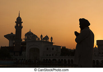 Silhouette of praying sikh man at golden temple of Amritsar, India