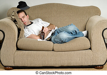 Sleeping With Beer - A young man sleeping on the couch with...