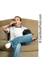 Relaxing - A young man watching some tv and drinking a...