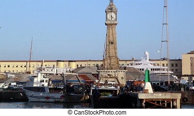 Clock tower near the port where some small boats are docks...