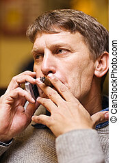Business matters - Mature man smoking cigar while speaking...