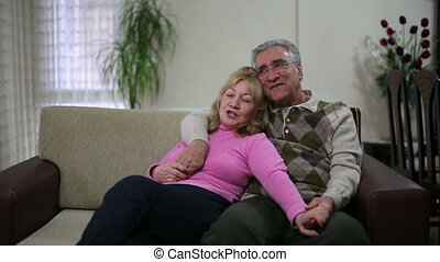 Senior couple sitting on sofa - Senior couple talking while...