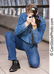 Photographer at work - Photographer with SLR camera at work;...