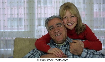 Senior couple sitting together - Senior couple laughing and...