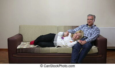 Senior couple together on sofa - Senior couple talking while...