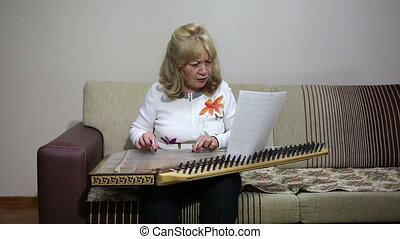 Senior woman playing qanun instrument - Senior woman playing...