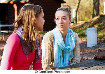 Giving advice - Two beautiful young women talking in the...