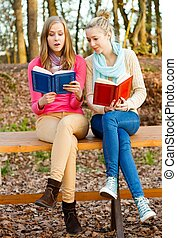 Reading is great - Two beautiful young women reading their...