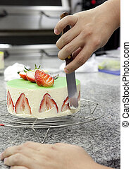 Hand of chef decorating cake