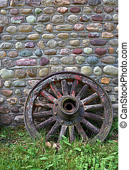 Wagon Wheel - Antique wagon wheel against cobblestone wall