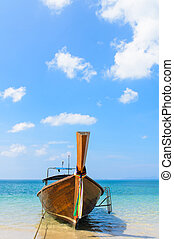 Thai Traditional longtail boat in the beach with blue sky...