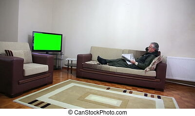 Senior man watching TV show while sitting on sofa in his...