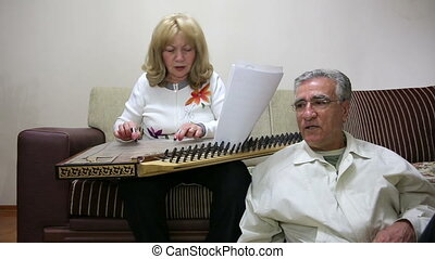 Senior woman playing qanun instrume