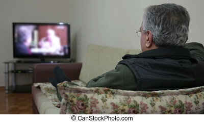 man watching TV show while sitting on sofa in her living...