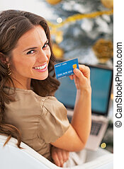 Portrait of smiling young woman with credit card using...