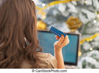 Woman making online shopping in front of christmas tree rear...