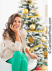 Thoughtful young woman sitting in front of christmas tree