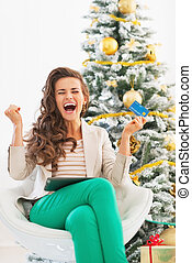 Happy young woman with credit card and tablet pc rejoicing