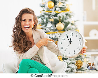 Happy young woman pointing on clock in front of christmas...