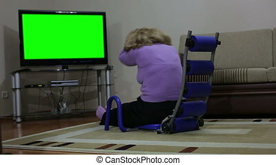 Senior woman exercising in front of TV