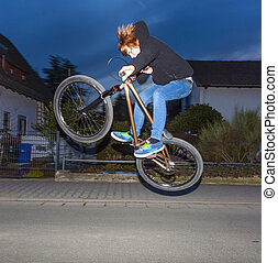 boy with dirtbike is going airborne by night