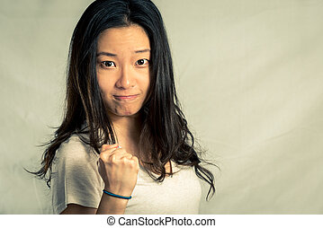 Young woman clenching her fist for encouragement, with...